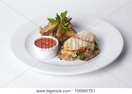 roasted meat with tomatoes and mayonnaise, potato wedges in the peel plate isolated white background