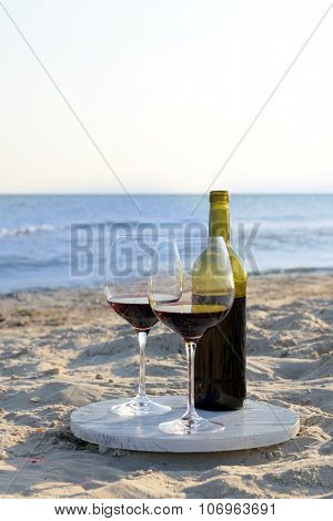 Wine bottle and glasses on the seashore