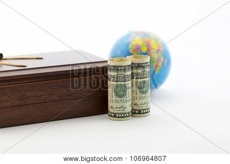 Focus On Currency And Wood Box With Globe In Background