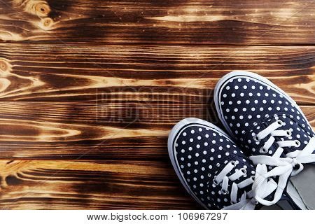 Female Gumshoes On Brown Wooden Background