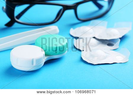 Contact Lenses In Container With Solution On Blue Background