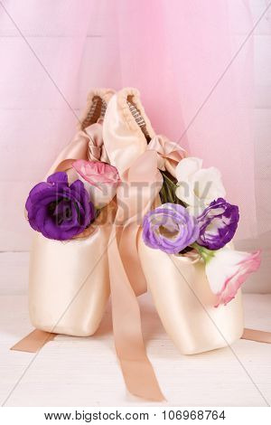 Decorated with flowers ballet shoes on rosy satin background