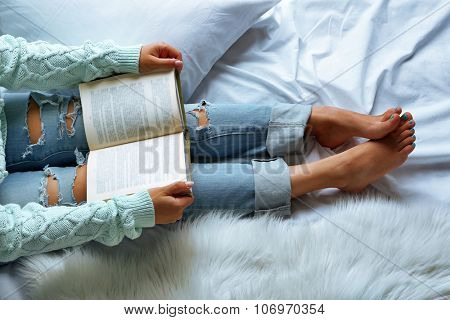 Woman in blue jeans reading book on bed top view point