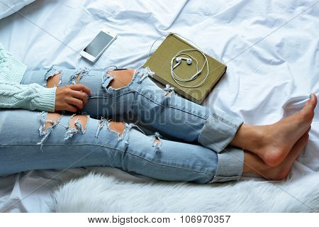 Woman in blue jeans with book and phone on bed top view point