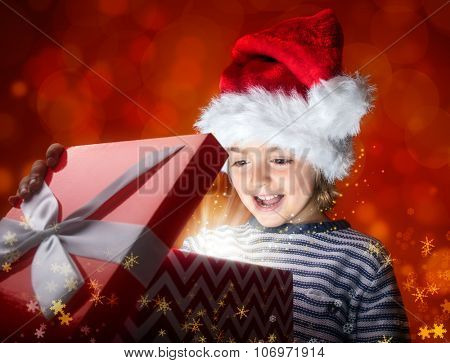 Boy opening a magical Christmas gift box getting a big surprise
