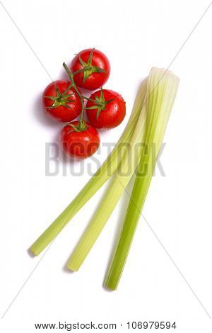 Bunch of fresh tomatoes and celery sticks, top view isolated on white background