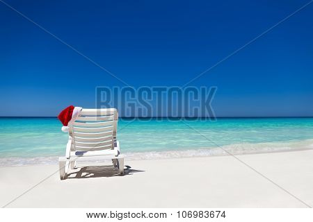 Santa Claus Hat On Sunbed Near  Tropical Calm Beach With Turquoise Caribbean Sea Water And White San