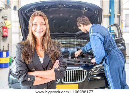Young business woman, smiling and looking into the camera, whilst a mechanic tends to the maintenance of her car in the background at a dedicated professional garage