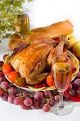 stock photo of roast chicken  - roasted chicken or turkey garnished with lemon cranberry apples tomatoes bread and wine - JPG