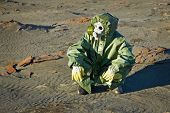 foto of scoria  - Scientist in a green protective suit and gas mask sitting on the slag - JPG