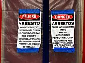stock photo of torte  - Bilingual asbestos warning signs on plastic covering a front door - JPG