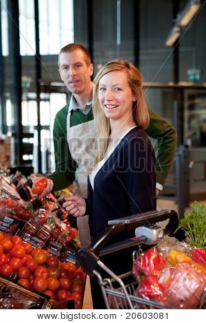 A woman buying fruit at a supermarket receiving help from a store clerk