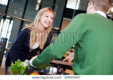 A man pushing a woman standing on a grocery cart