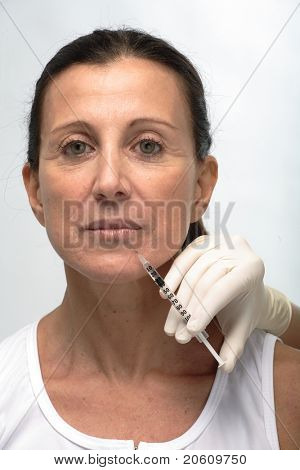 Mature attractive woman and a syringe of