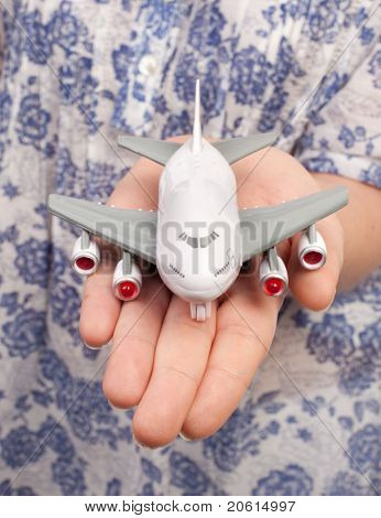 Woman hand with a small plane