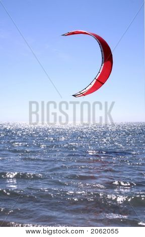 Red Kite Surfer Sail against a blue sky hanging just above the surf. : Bigstock