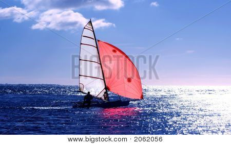 Red Sail, dinghy sailing into the sun on a blue sea : Bigstock