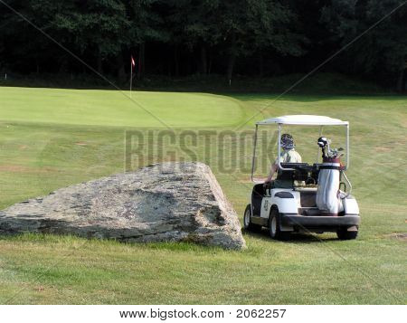 Golfer In Golf Cart Near Boulder On Fairway