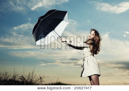 Fashion Portrait Of Elegant Woman In A Raincoat On The Nature