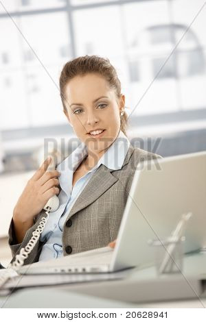 Young attractive businesswoman sitting by desk in bright office, holding away phone while checking information on laptop, smiling.?