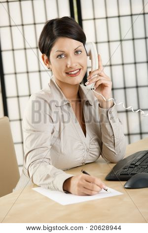 Young businesswoman sitting at desk in office, talking on phone, writing notes, smiling.?