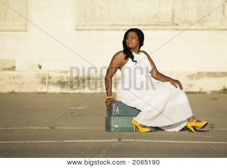 African American Woman Sitting On Suitcases