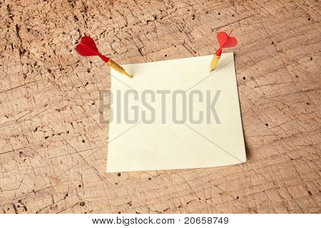 Red darts in an empty or blank notepad on a vintage wooden board