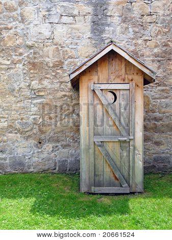 Rustic outhouse with vintage stone wall
