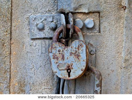 Rusty Padlock On An Old Metal Door