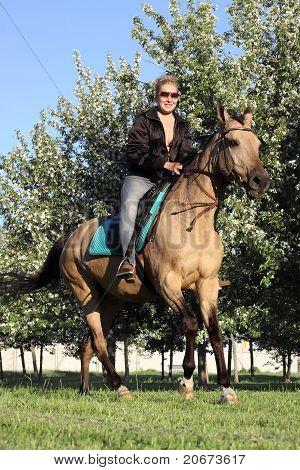 Woman On Horseback In A Blooming Garden