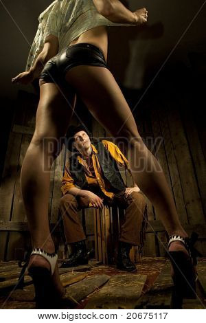 Young Cowboy looking at woman taking off her clothes against wooden background