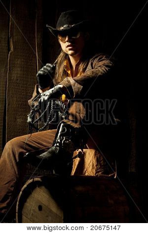 Cowboy with Black Leather Flogging Whip in his hand against wooden background