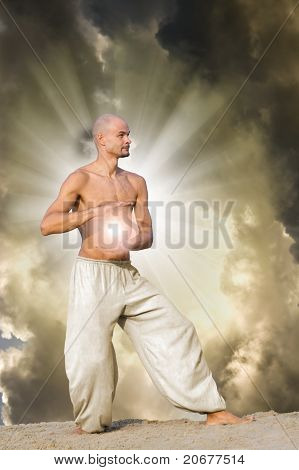 Man Practises Tai Holding A Ball Of Energy With Dramatic Cloudy Sky And  Sun Rays In Background