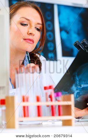 versonnen Arzt Frau am Schreibtisch sitzend und suchen Patienten Röntgen