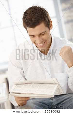 Young businessman happy about news reading in papers, raising fist, laughing.?