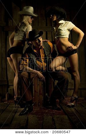 Young cowboy with pair cowboy girls against wooden background