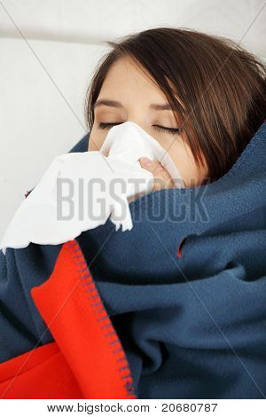Young woman at home having flu, wrapped up in blanket, sneezing.