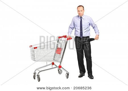 A bankrupt businessman turns out his empty pocket and an empty shopping cart isolated on white