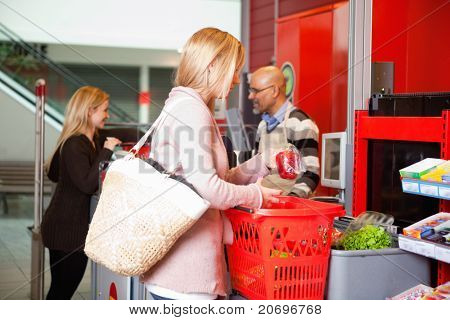 Customer shopping in supermarket with people in the background