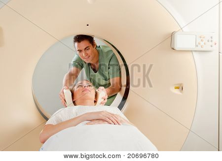 A CT Scan Technician preparing a patient for scanning