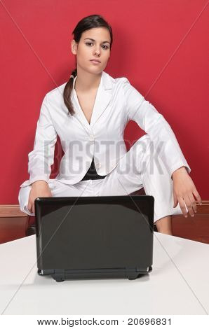 Portrait of smart businesswoman posing in front of laptop on table