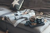 Still life details of living room. Cup of coffee on rustic wooden tray, candle and warm woolen sweat poster