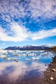 Clouds reflected in the water of lagoon. The ice floes and cirrocumulus clouds of lagoon Jokulsarlon poster