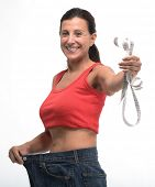 stock photo of ordinary woman  - Happy woman in old jeans pant after losing weight - JPG
