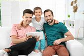 Male gay couple with foster son resting at home. Adoption concept poster