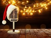 Microphone with Santa hat and garland on background. Christmas music concept poster