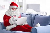 Santa Claus with laptop and credit card on sofa at home poster
