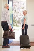 Senior couple with luggage leaving home for a holiday poster