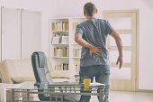 Man in home office suffering from low back pain standing near desk with notebook, papers and other o poster