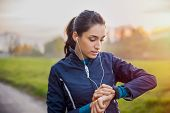 Young athlete listening to music during workout at park and adjusting smart watch. Young latin woman poster